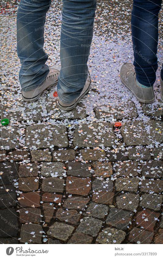 Drei Beine ins Jeans und Turnschuhen, stehen auf der Straße in Konfetti, an Fasching / Karneval. Füße jeans konfettiregen Feier Feiern Fasnet Feste & Feiern