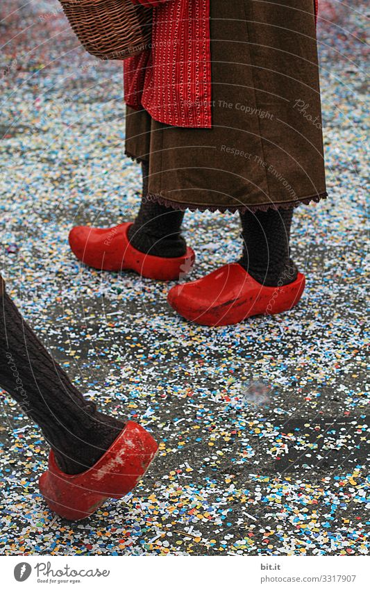 Drei Beine stehen und laufen in roten holländischen Klompen; Holzschuhen und Schürze verkleidet auf der Straße mit Konfetti bedeckt, an Fasching bei einem Karnevalsumzug, der traditionellen Buernfasnachtin Südbaden.