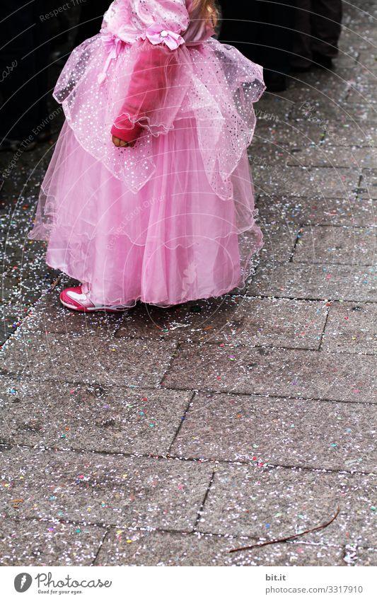 Kleine verspielte, verträumte, hübsche, schöne, süße, verkleidete Prinzessin im rosa, pinken Kleid mit Tüll, steht an Fasching, Karneval als Zuschauer, Besucher am Karnevalszug auf der Straße, auf Konfetti und schaut, beobachtet, genießt das Fest.