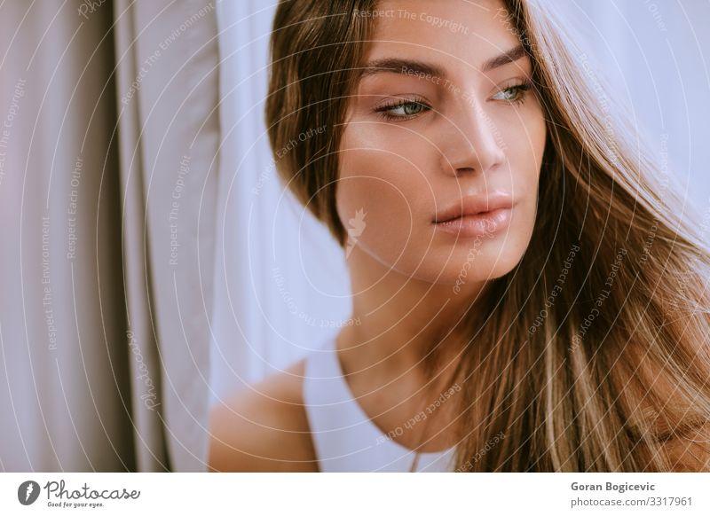 Hübsche junge Brünette mit langen Haaren vor dem Fenster Lifestyle Stil Glück schön Haare & Frisuren Haut Gesicht Mensch Junge Frau Jugendliche Erwachsene
