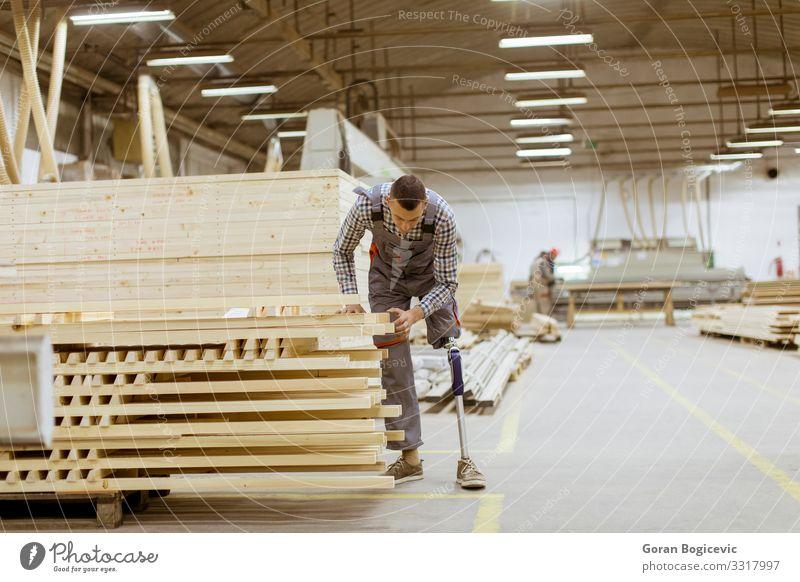 Behinderter junger Mann mit Beinprothese in der Möbelfabrik Arbeit & Erwerbstätigkeit Beruf Handwerker Arbeitsplatz Fabrik Industrie Business Werkzeug