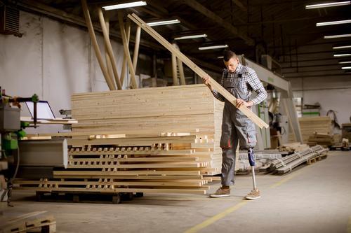 Behinderter junger Mann mit einer Beinprothese in der Möbelfabrik Arbeit & Erwerbstätigkeit Beruf Arbeitsplatz Fabrik Industrie Business Werkzeug Erwachsene