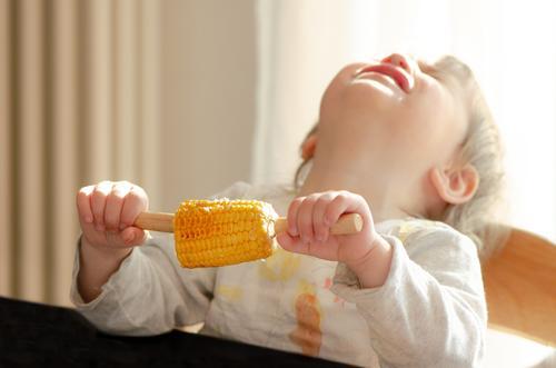Kind hält Mais in der Hand und wirft weinend den Kopf nach hinten Lebensmittel Gemüse Maiskolben Essen Mensch feminin Kleinkind Mädchen 1 1-3 Jahre festhalten
