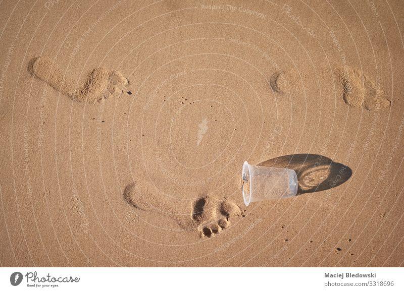 Fußabdrücke und Plastikbecher an einem Sandstrand. Lifestyle Ferien & Urlaub & Reisen Tourismus Sommerurlaub Strand Umwelt Natur Kunststoff Fußspur