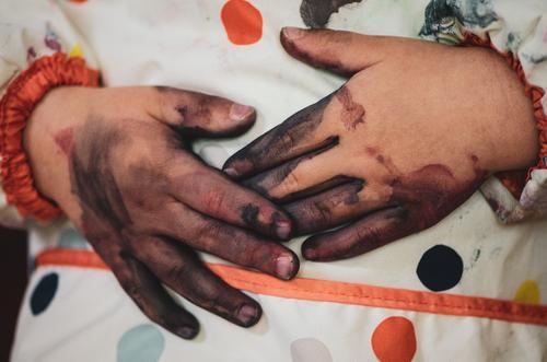 Angemalte Hände liegen auf Schürze Mensch Kind Kleinkind Kindheit Hand Finger 1 1-3 Jahre 3-8 Jahre berühren festhalten authentisch dreckig Zusammensein nah
