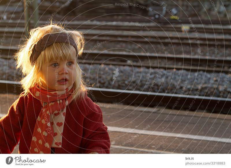 Blondes Mädchen mit Kulleraugen, Strirnband & Schal, steht im herbstlichen sanften Abendlicht am Bahngleis und wartet auf Besuch. Neugieriges, fröhliches Kind in warmer Kleidung, wartet im abendlichen Sonnenlicht am Bahnsteig. Reisen, Fahren mit Bahn, Zug.