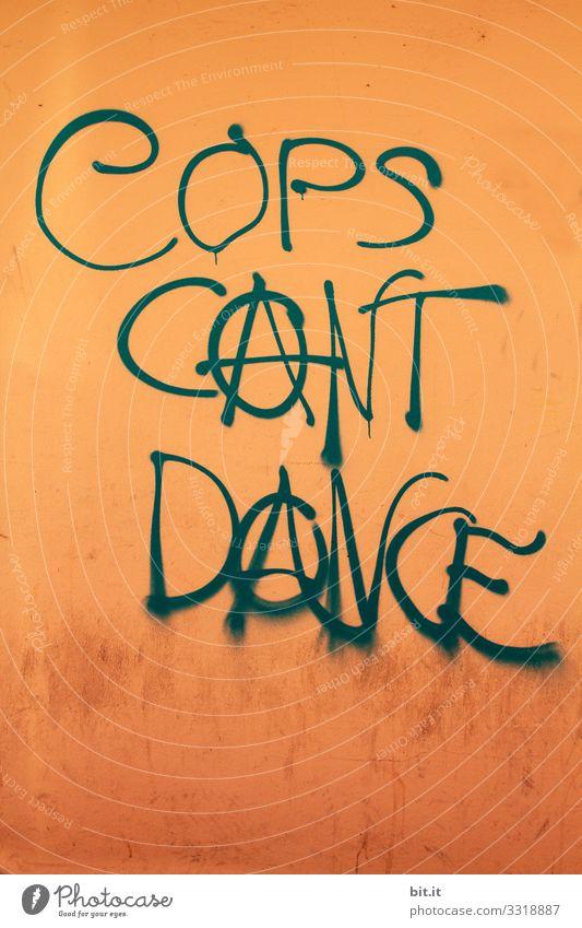 Die Polizei kann nicht tanzen, steht als Schriftzug auf oranger Wand geschrieben. Ironisches Schriftzeichen gegen Polizei, für Anarchie mit Anarchiezeuchen auf Wand gesprayt. Symbol für Anarchismus, Politik ohne Macht, Linke, Freiheit und Linksbewegung.