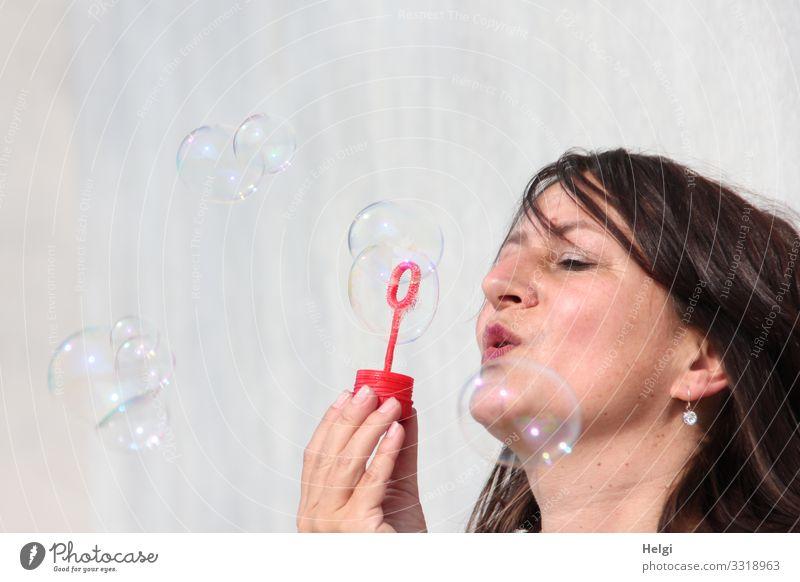 Gesicht einer Frau mit brünetten langen Haaren pustet Seifenblasen Mensch feminin Erwachsene Kopf Hand 1 45-60 Jahre Mauer Wand langhaarig Bewegung festhalten