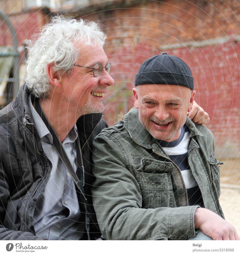 Porträt von zwei lachenden Senioren, einer mit sibergrauen Locken und Brille, der andere mit Mütze vor einer alten Wand Mensch maskulin Mann Erwachsene 2