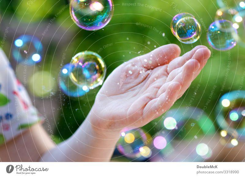 Fliegende Seifenblasen, die in der Hand zerplatzen Freizeit & Hobby Spielen Kinderspiel Mensch 3-8 Jahre Kindheit 8-13 Jahre 13-18 Jahre Jugendliche berühren
