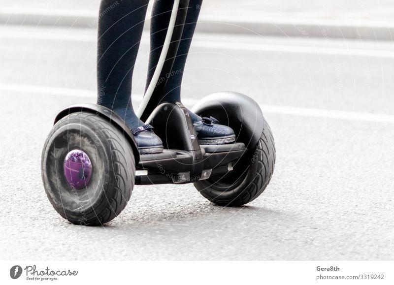 weibliche Beine auf einem Elektroroller auf einer Stadtstraße aus nächster Nähe Frau Erwachsene Verkehr Straße Bekleidung Schuhe gebrauchen Großstadt elektrisch