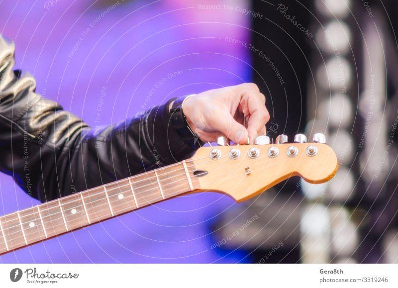 männlicher Handmusiker stimmt Gitarre aus nächster Nähe Spielen Musik Mann Erwachsene Finger Konzert Musiker Felsen Bekleidung Jacke schwarz Farbe Hintergrund