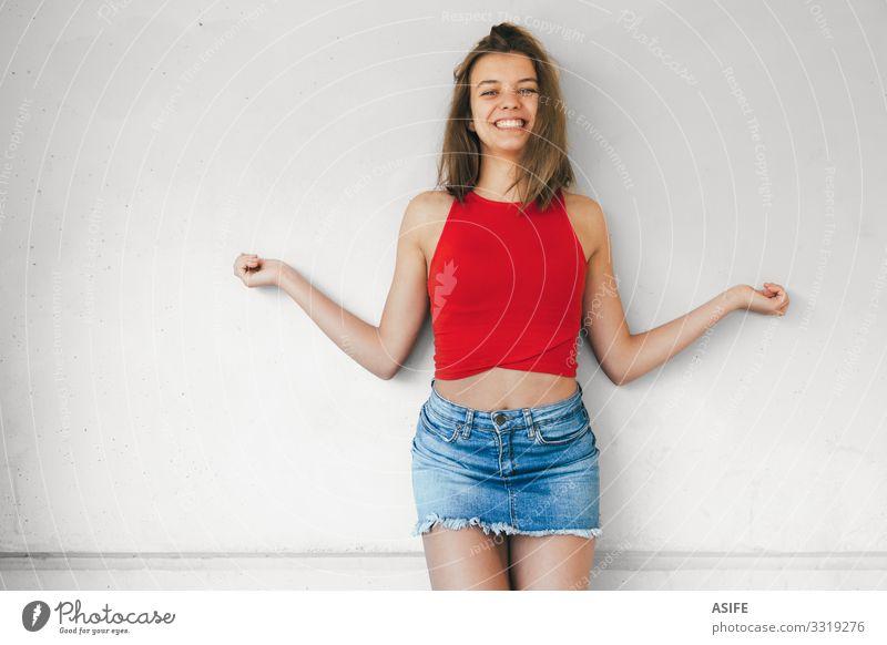 Fröhliche Teenagerin lacht mit offenen Armen Freude Glück schön Gesicht Frau Erwachsene Jugendliche Zähne Mode brünett Beton Lächeln lachen niedlich rot weiß