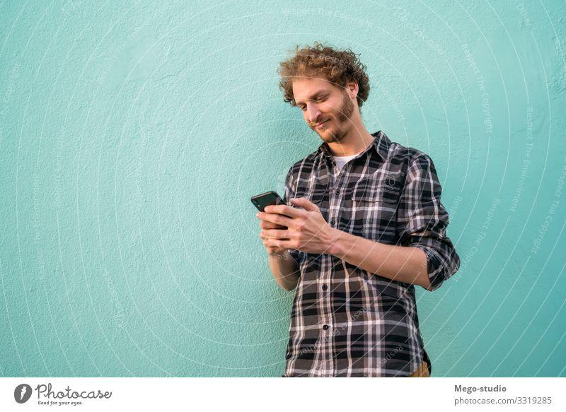 Porträt eines jungen Mannes mit seinem Mobiltelefon vor blauem Hintergrund. Konzept der Kommunikation. Lifestyle Stil Freude Glück Zufriedenheit Telefon PDA
