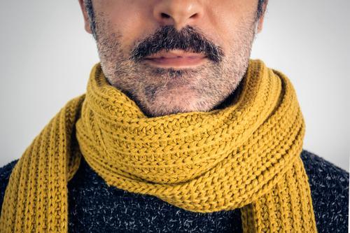 Nahaufnahme eines braunen Mannes mit Schnurrbart und gelbem Schal. Erwachsene schön Krebs Freizeitbekleidung Kaukasier charmant Erkältung Coolness Ausdruck