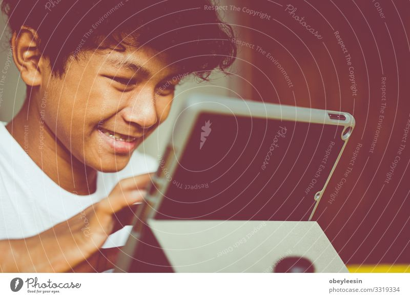 asiatischer Junge hat eine gute Zeit mit seiner Tablette Freude Glück Spielen lesen Sommer Garten Schlafzimmer Kind Computer Technik & Technologie Internet