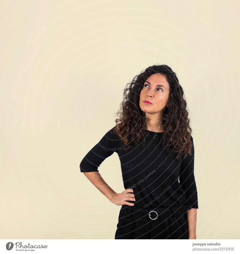 Brünette Frau schaut mit nachdenklicher Geste auf 30-45 Jahre Einstellung Beautyfotografie braun Freizeitbekleidung Konzentration krause Haare
