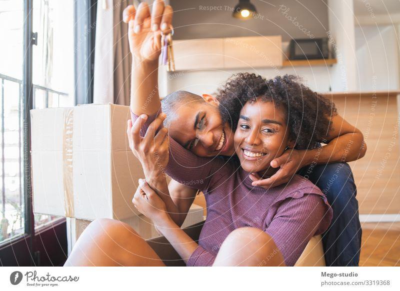 Lateinamerikanisches Ehepaar amüsiert sich mit Pappkartons im neuen Haus. Lifestyle Freude Glück schön Erholung Wohnung Umzug (Wohnungswechsel) Mensch Frau