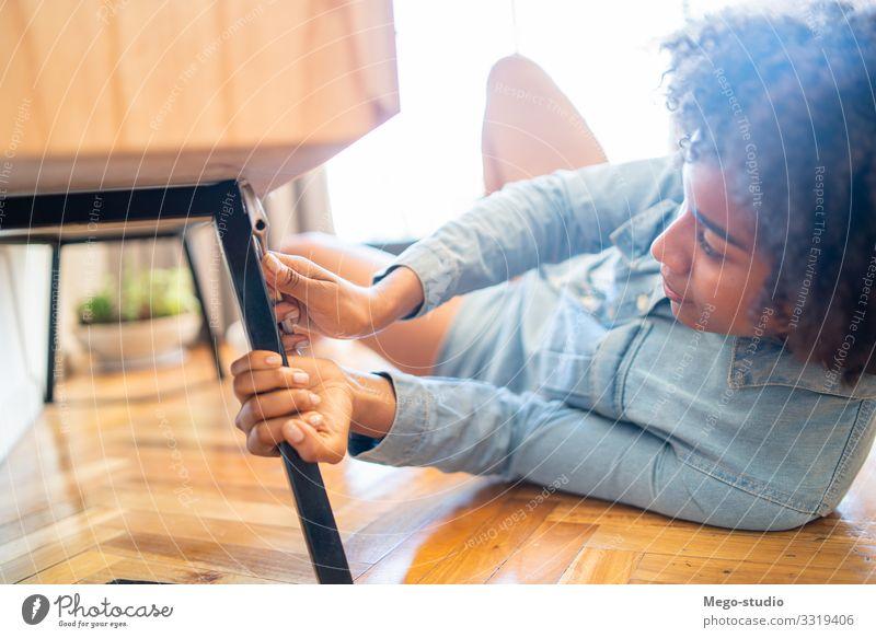 Afrofrau, die zu Hause Möbel repariert. Lifestyle Arbeit & Erwerbstätigkeit Werkzeug Frau Erwachsene Hand Reinigen Reparatur Mechanikerin bohren gebrochen