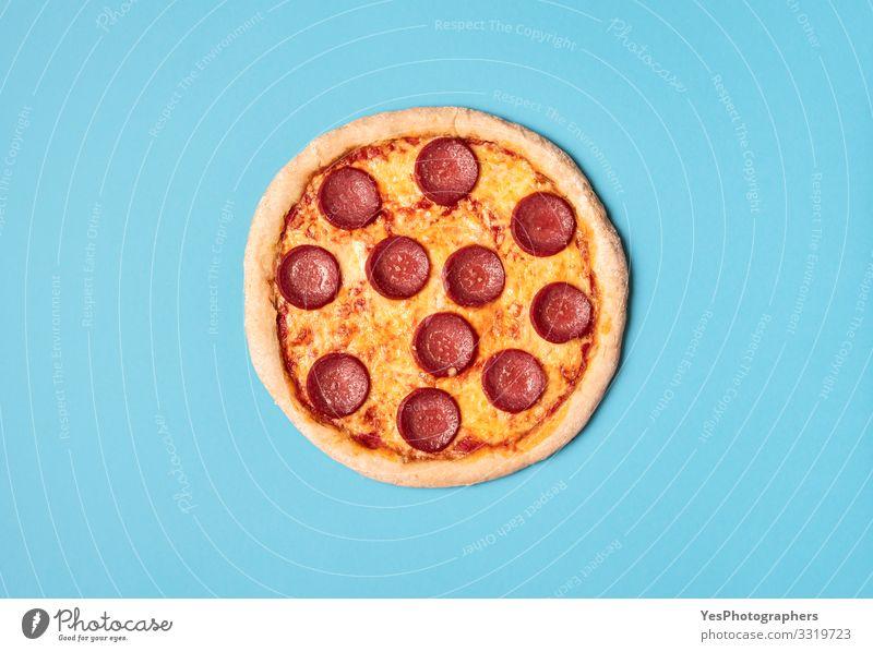 Pizzasalami auf blauem Hintergrund. Ganze Pizza mit Peperoni. Lebensmittel Teigwaren Backwaren Ernährung Mittagessen Abendessen Fastfood Fingerfood