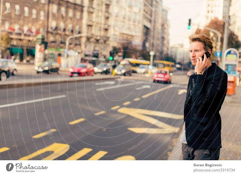 Junger Mann auf der Straße mit Mobiltelefon Lifestyle Telefon PDA Technik & Technologie Mensch Jugendliche Erwachsene Herbst Gebäude Vollbart stehen