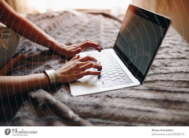 Die Hände der Frau beim Tippen auf der Laptop-Tastatur im gemütlichen Schlafzimmer. Lifestyle Studium Arbeit & Erwerbstätigkeit Beruf Arbeitsplatz Büro