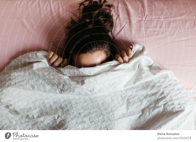 Verspielte junge Frau, die ihr Gesicht unter einer Decke versteckt Erholung Erwachsene Lächeln schlafen lang Gefühle Scham Angst Stress bequem erschrecken