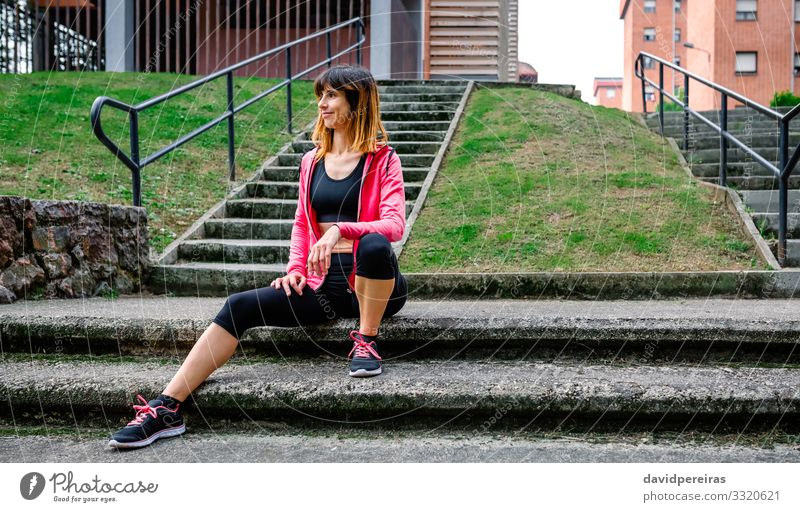 Sportlerin posiert sitzend auf der Treppe im Freien Körper Joggen Mensch Frau Erwachsene Gras Turnschuh Fitness Lächeln dünn natürlich Athlet urban Mädchen jung