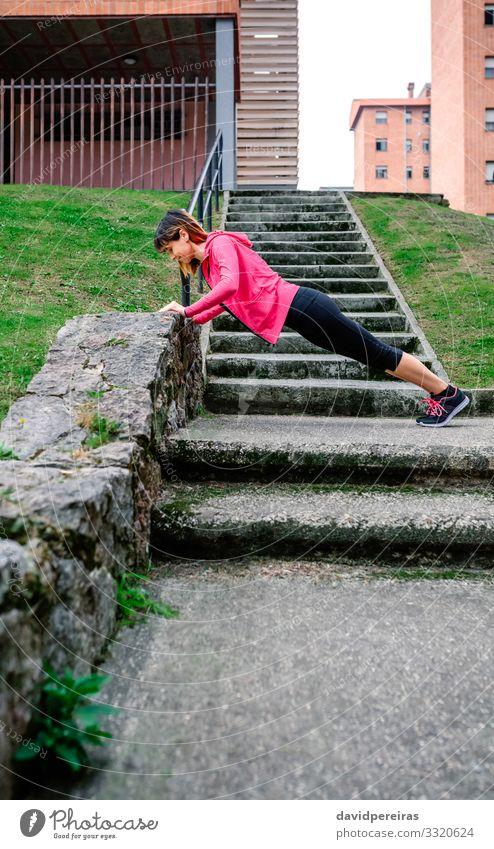 Sportlerin macht Liegestütze im Freien Glück Körper Mensch Frau Erwachsene Gras Turnschuh Fitness dünn natürlich unterstützt Wand Treppe urban Training üben
