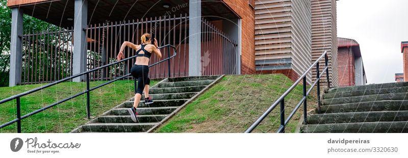 Sportlerin, die im Freien eine Treppe hinaufsteigt Klettern Bergsteigen Joggen Internet Mensch Frau Erwachsene Turnschuh Fitness dünn Athlet rennen treppauf