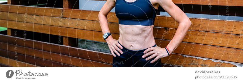 Fröhliche Sportlerin vor einem hölzernen Hintergrund Lifestyle Körper Internet Mensch Frau Erwachsene brünett Fitness stehen sportlich authentisch dünn muskulös