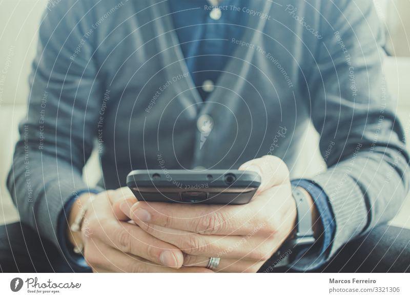 kaukasischer Mann mit Handy in der Hand Lifestyle Häusliches Leben Wohnung Innenarchitektur Sofa Uhr Technik & Technologie Telekommunikation Internet Mensch