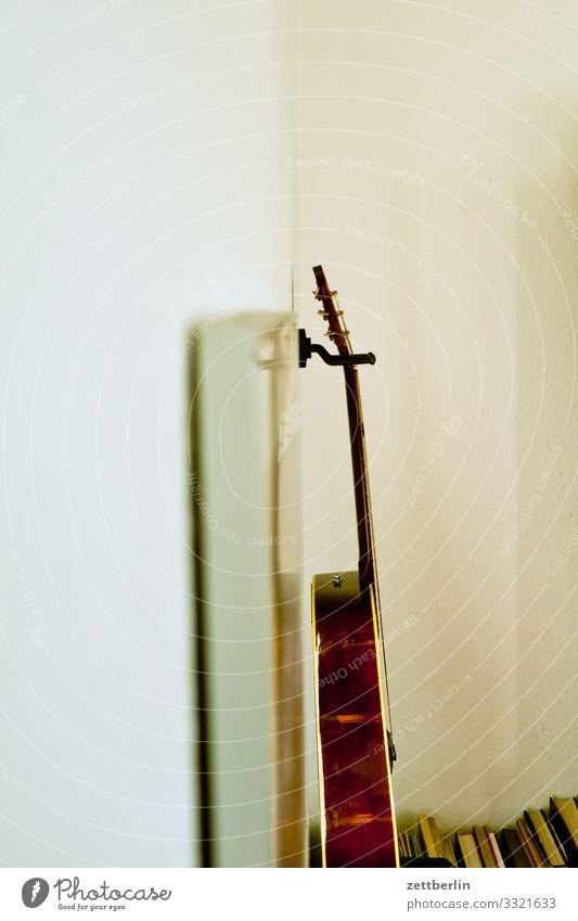 Gitarre an der Wand Musik Musikinstrument Saiteninstrumente hängen Wohnung Raum Innenarchitektur Ecke Nische aufbewahren Halterung Seite Profil seitwärts