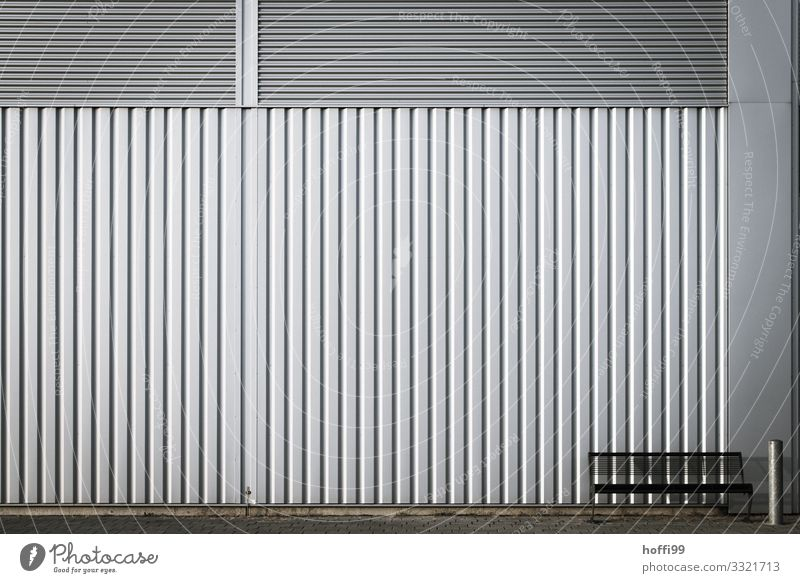einsame Bank mit Ascher vor Wellblech Fassade Haus Industrieanlage Architektur Mauer Wand Aschenbecher Metall Stahl Linie sitzen warten ästhetisch einfach