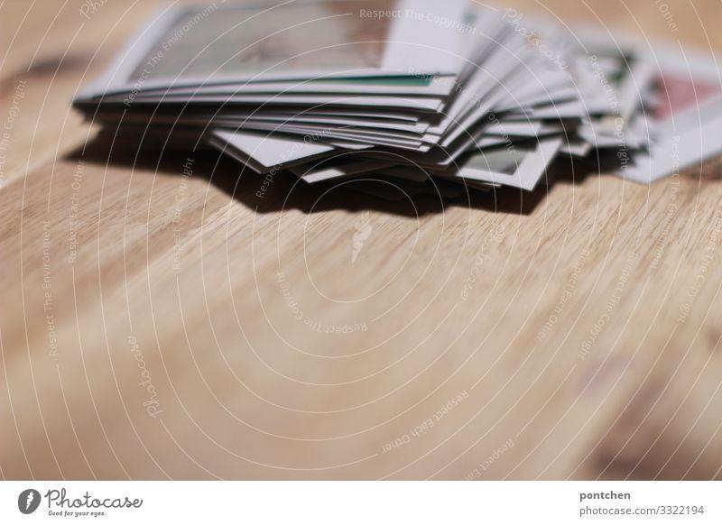 Stapel von polaroidfotos auf holztisch Sammlung entdecken liegen Blick Polaroids Fotografie Rahmen Tisch Erinnerung retro altmodisch trendy Holz Holztisch viele