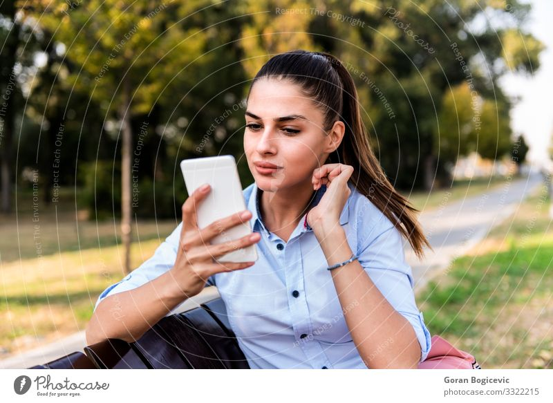 Hübsches junges Mädchen auf einer Bank sitzend mit Mobiltelefon Lifestyle Glück schön Sommer Sonne Telefon PDA Technik & Technologie Mensch Junge Frau
