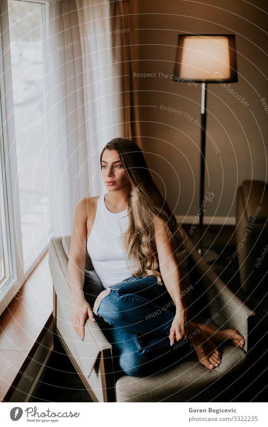 Hübsche junge Frau am Fenster sitzend Lifestyle schön Erholung Wohnung Haus Mensch Junge Frau Jugendliche Erwachsene 1 18-30 Jahre Hemd brünett lang niedlich