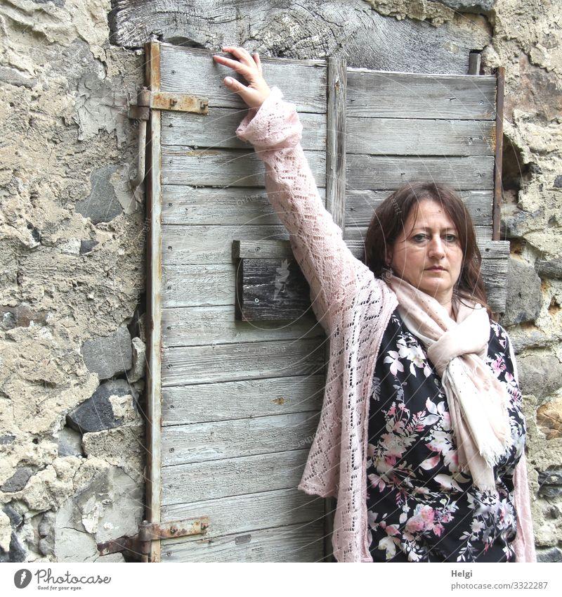 langhaarige brünette Frau mit gemustertem Kleid, rosa Jacke und rosa Schal steht vor einer Wand mit altem geschlossenen Holzfenster Mensch feminin Erwachsene 1