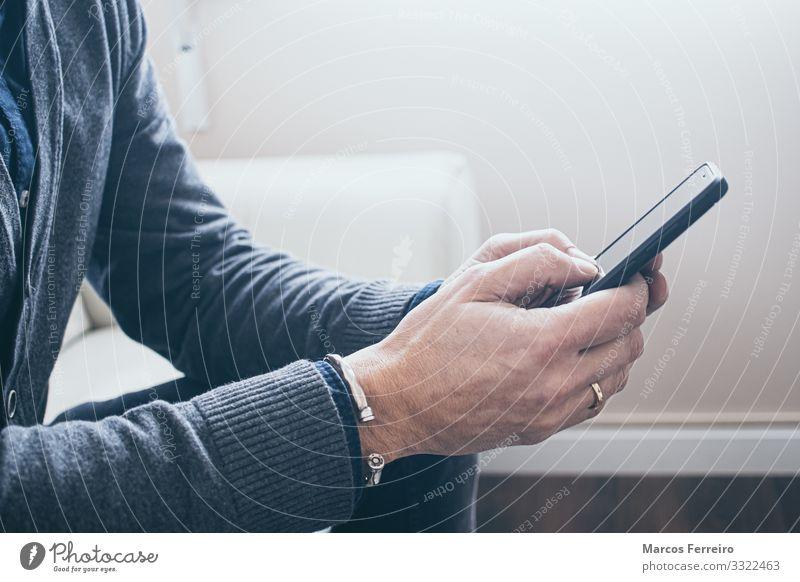 Mann mit Smartphone auf dem Sofa Lifestyle Stil Freude Häusliches Leben Innenarchitektur Handy Technik & Technologie Unterhaltungselektronik Telekommunikation