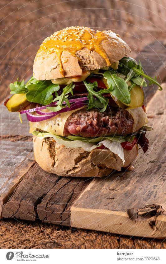 Cheeseburger Fleisch Käse Gemüse Brot Brötchen Mittagessen Tisch Holz dunkel frisch lecker hamburger rustikal Speck geröstet brioche Brennpunkt selektiv