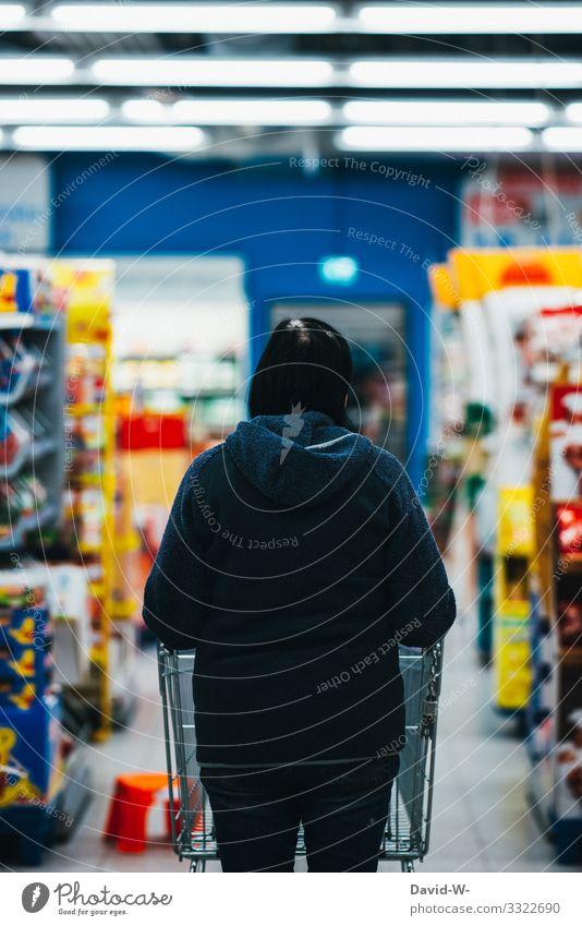 Frau geht mit dem Einkaufswagen durch das Geschäft Lebensmittel einkaufen Supermarkt Farbfoto Konsum Ladengeschäft Mensch verbraucher hand legen Verbraucher