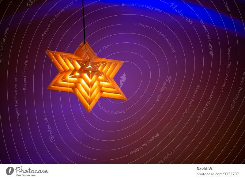 ein leuchtender Stern hängt von der Decke vor blau beleuchtetem Hintergrund Weihnachten schön Holzstern farbenfroh hängen Weihnachten & Advent