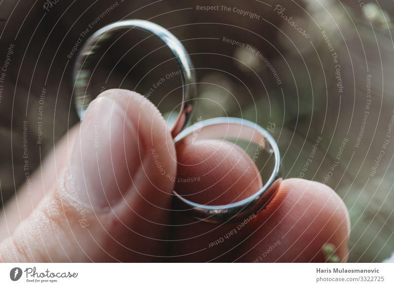 Trauringe in der Hand halten Makro in Nahaufnahme auf verschwommenem Hintergrund Hochzeit Schmuck Ring gold träumen schön Zusammensein Liebe Farbfoto
