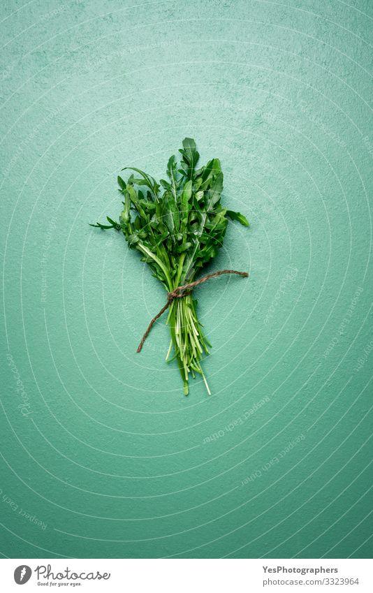 Frische Rucola-Blätter in einem Strauß auf grünem Tisch. Rucola-Bündel Gemüse Salat Salatbeilage Bioprodukte Vegetarische Ernährung Diät Gesunde Ernährung