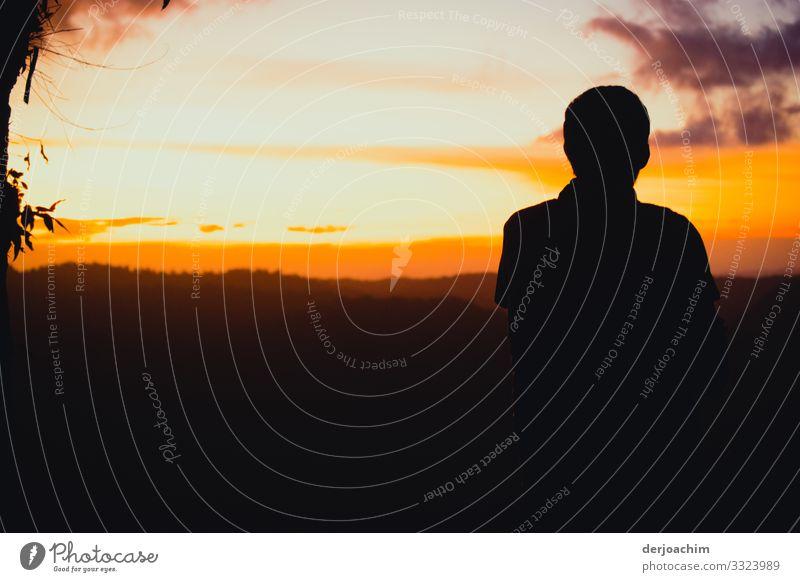 Hauptsache / Sonnenuntergang sehen. Die Landschaft ist in vielen Farben zu sehen. Eine Kontur von einer Person ist mit dem Rücken zum Bild. Freude Wohlgefühl