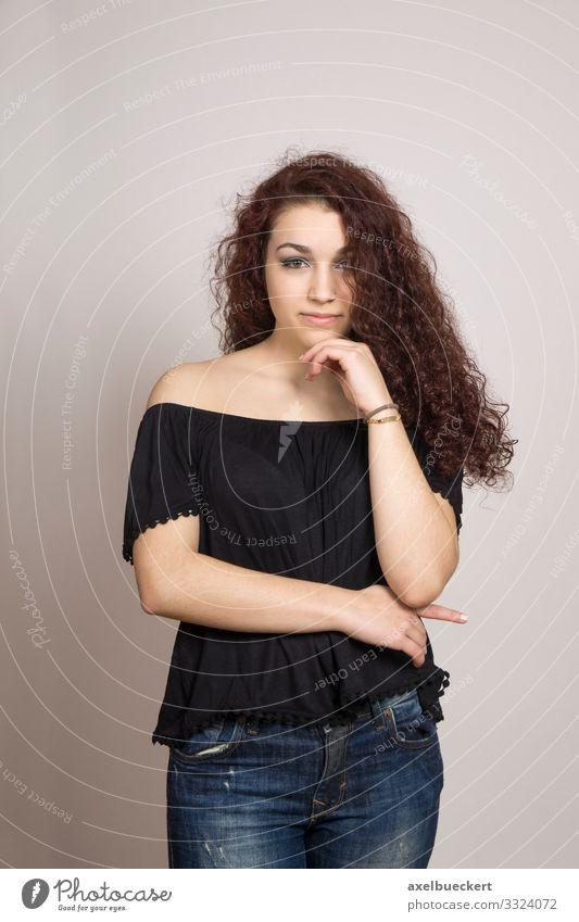 nachdenkliche junge Frau mit langem lockigem Haar Mensch feminin Junge Frau Jugendliche Erwachsene 1 13-18 Jahre 18-30 Jahre Jeanshose Bluse brünett langhaarig