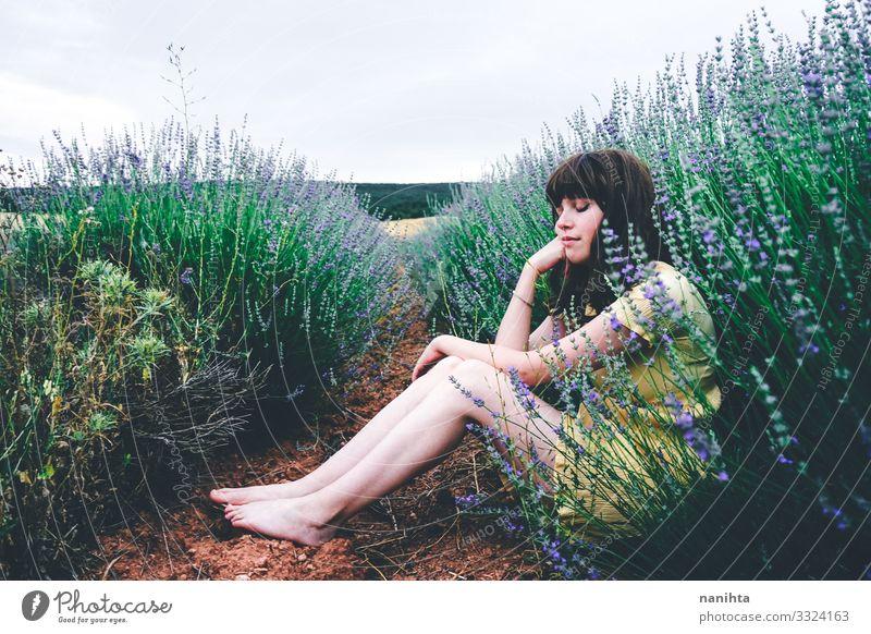Junge brünette Frau sitzt umgeben von Lavendel Lifestyle schön Leben Erholung ruhig Freiheit Sommer Mensch feminin Junge Frau Jugendliche Erwachsene 1 Natur