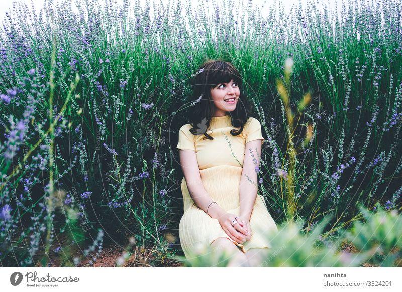 Junge brünette Frau sitzt umgeben von Lavendel jung hübsch retro altehrwürdig Natur natürlich wirklich offen sich[Akk] entspannen Ruhe Szene Blumen Frühling