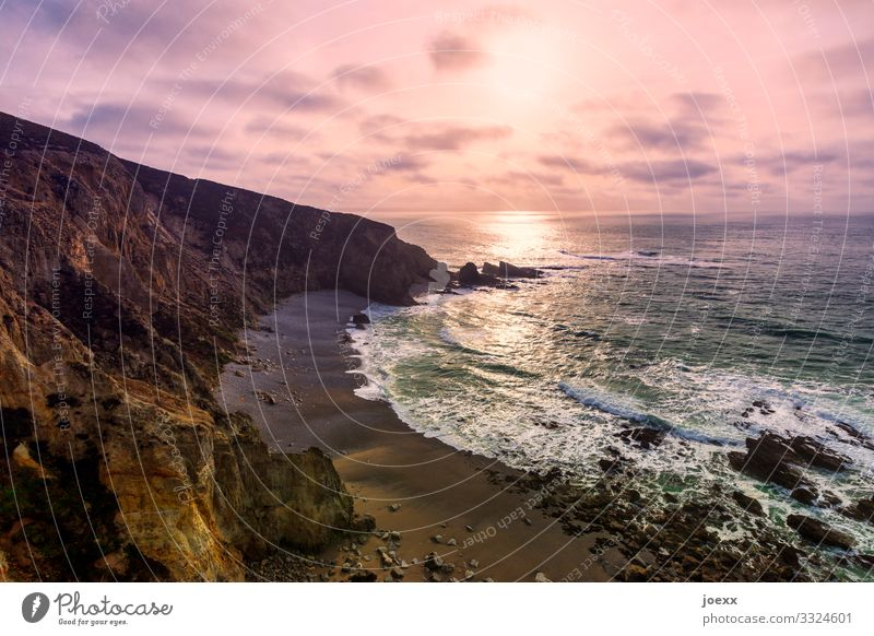 Steile Küste mit felsigem Strand und Brandung vor rosa Wolkenhimmel Meer Wellen Natur Landschaft Himmel Schönes Wetter Felsen gigantisch groß maritim braun weiß