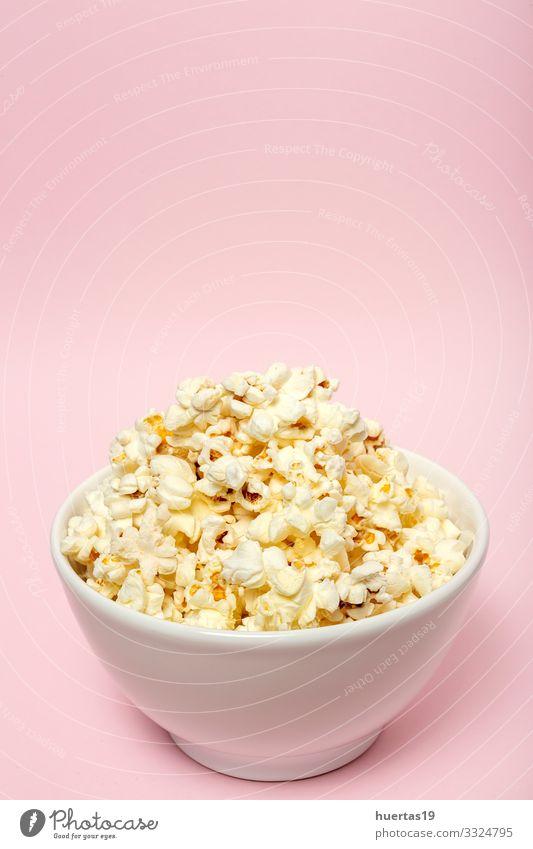 Popcorn auf farbigen Hintergründen Lebensmittel Fastfood Schalen & Schüsseln Entertainment Kino frisch lecker rosa weiß Farbe Popkorn Snack Mais salzig